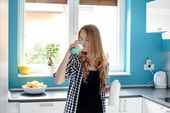Thirsty young blond woman drinking milk — Stock Photo