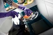 Woman's hands cleaning kitchen top in protective gloves — Stock Photo