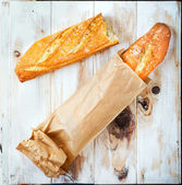 Baguette in a grocey paper bag. Loaf of bread — Stock Photo