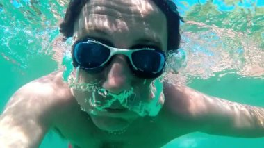 Slow motion of a man breathing out air bubbles underwater — Stock Video