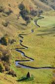 Autumn mountain landscape with a small meandering water stream — Stock Photo