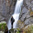 Tourist standing in the front of a waterfall — Stock Photo #55948083