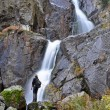 Tourist standing in the front of a waterfall — Stock Photo #55948085