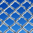 Fence covered by ice crystals against blue sky — Stock Photo #56703355