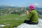 Girl playing on flute in the mountains — Stock Photo