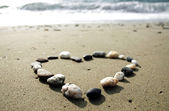 Heart made of small stones on sand — Stock Photo
