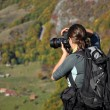 Woman photographer taking a photo in the mountains at autumn — Stock Photo #72754761