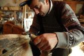 Carpenter handcrafting a wooden alpenhorn — Stock Photo