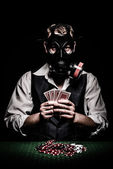 Poker player with a gas mask on his head — Stock Photo