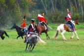 Reenactors dressed as Napoleonic war soldiers ride horses — Stockfoto