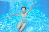 Child swims in swimming pool, playing and having fun, underwater and above view — ストック写真