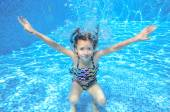 Child swims in swimming pool, playing and having fun, underwater and above view — Stock Photo