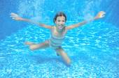 Child swims in swimming pool, playing and having fun, underwater and above view — Foto de Stock