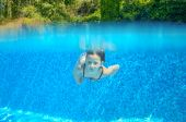 Child swims in swimming pool, playing and having fun, underwater and above view — Стоковое фото