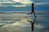 Silhueta do corredor de mulher correndo na praia do sol com reflexão — Fotografia Stock