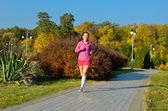 Woman running in autumn park, beautiful girl runner jogging outdoors — Stock Photo