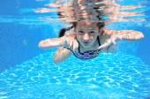 Happy girl swims in pool underwater, active kid swimming — Стоковое фото