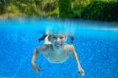Happy girl swims in pool underwater, active kid swimming — Foto Stock