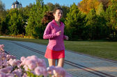 Woman running in autumn park, beautiful girl runner jogging outdoors — Stockfoto