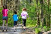 Family sport, happy active mother and kids jogging outdoors, running in forest — Stock Photo