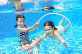 Happy children swim in pool underwater, girls swimming, playing and having fun, kids water sport — Stock Photo