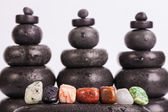 Row Of Chakra Crystals on hot massage stones — Stock Photo