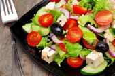 Greek salad and fork — Stock Photo