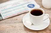 Cup of coffee and newspaper on a wooden table  — Foto Stock