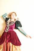 Actress in a medieval dress posing against a wall on a light background — Stock Photo
