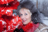 Beautiful woman in winter fur hat on a red background Christmas tree — Stock Photo