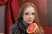Young girl with half a grapefruit in hands on a background of interior cafe — Stock Photo
