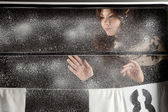 Young happy girl behind snow window on black background — Stock Photo