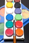 Brush and colored paint artist on gray background — Stock Photo