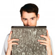 Young man looks out from behind folders isolated — Stock Photo #59721971