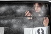 Menina bonita sobre a janela coberta de neve — Fotografia Stock