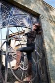 Girl with big eyes on a lattice wrought iron gates — Стоковое фото