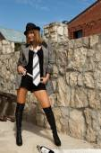 Women with cigarette and bottle of wine in hat and boots stand — Stock Photo