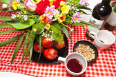 Celebratory table red wine flowers apples pistachios — Stock Photo