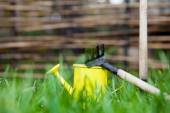 Yellow watering can in green grass — Stock Photo