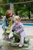 Mother and daughter sprayed water in the park — Stock Photo