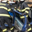Постер, плакат: Firefighters removing the cutting doors from a car wreck