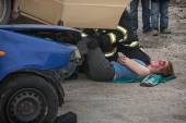 Firefighters saving the bleeding woman from a crashed car — Stock fotografie