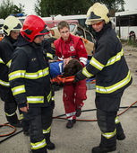 Firefighters and rescuers taking away injured on a stretcher by — Stock Photo