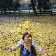Young caucasian woman throwing yellow leaves — Stok fotoğraf #57722219