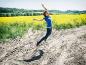 Positive young woman is jumping in rapeseed field — Stock Photo