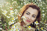 Young caucasian brunette woman in daisy meadow — Stock Photo