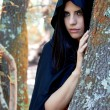 Beautiful fantasy woman wit black hood in the woods — Stock Photo #55430847