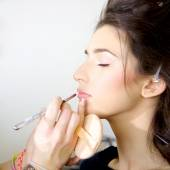 Female model getting makeup before photo shoot — Stock Photo