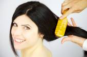 Happy woman getting long hair combed and new hairdo — Stock Photo