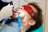 Closeup of man getting teeth whitened by dentist — Stock Photo